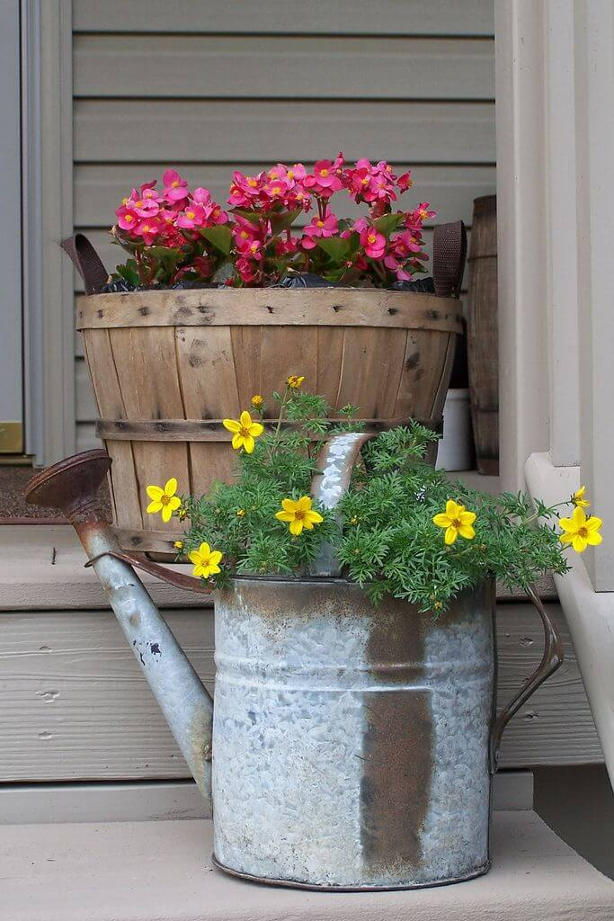 Pink and Yellow Flowers in a Barrel and Watering Cans
