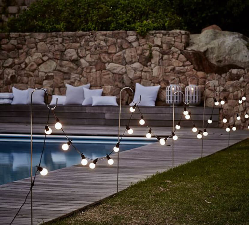 Globe Lights Hung On Hooks by the Pool