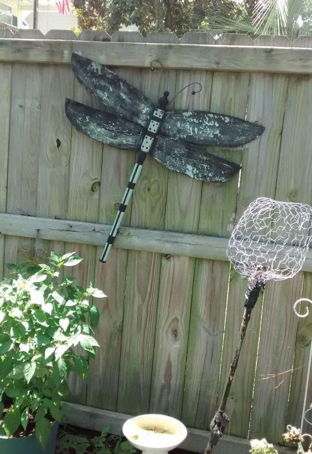 Weathered Dragonfly Sign on the Fence