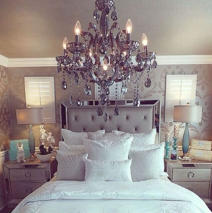 A Grey Chandelier and Satiny Bed Settings Give this Bedroom a Regal Feel